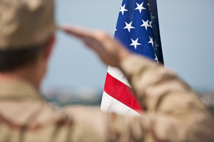 Soldier saluting an American flag