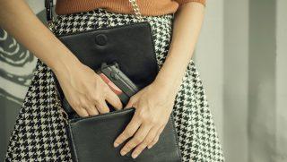 A woman pulls a gun from her purse.