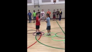 Two boys play rock, paper, scissors while standing in hoops.