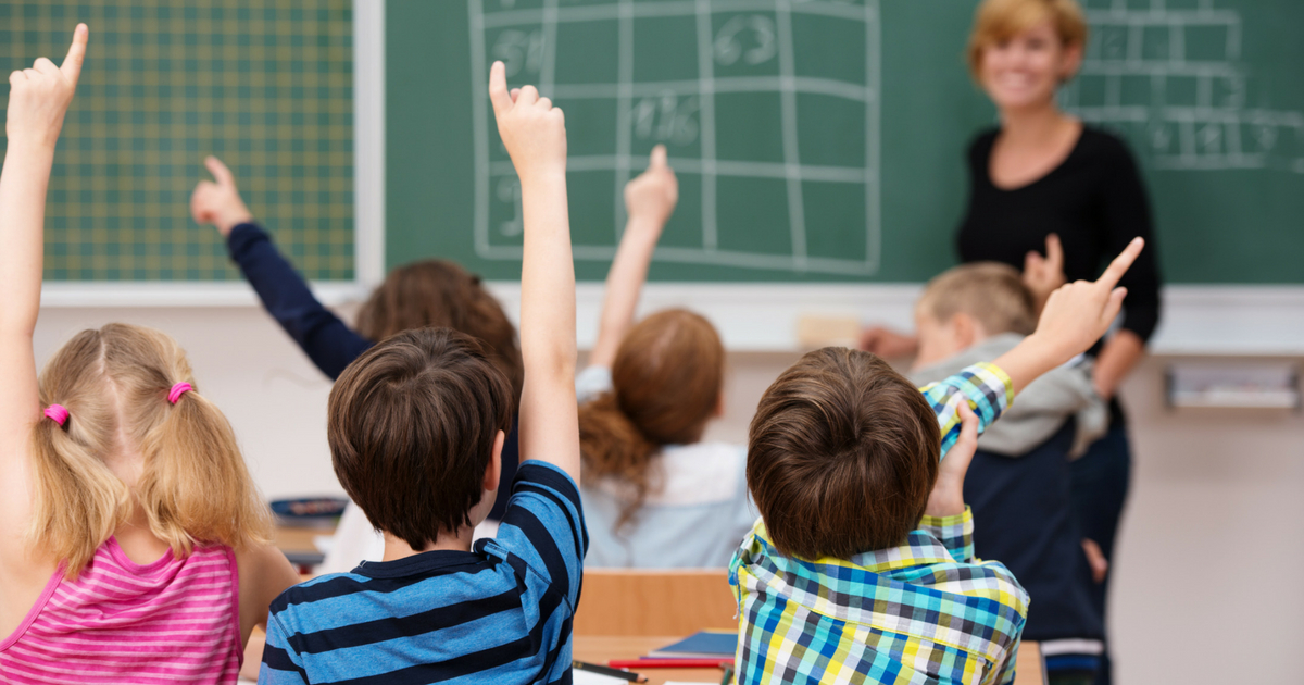 Group of young schoolchildren raising their hands to answer a question posed by the female teacher