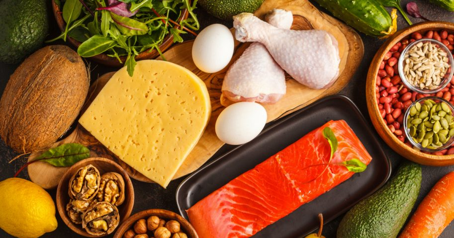 Ketogenic diet food -- vegetables, fish, meat, cheese and nuts -- displayed on a dark background.