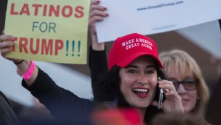 A woman hoods a sign expressing Latino support for Republican presidential candidate Donald Trump at his campaign rally at the Orange County Fair and Event Center, April 28, 2016, in Costa Mesa, California.