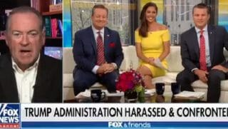 "Mike Huckabee in split screen with ""Fox & Friends"" crew."
