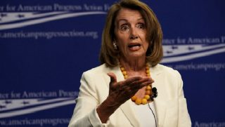 Pelosi gestures while speaking on a stage