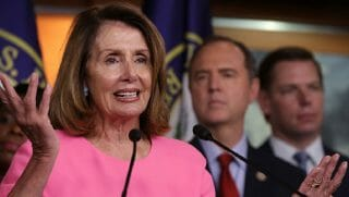 Nancy Pelosi speaking into a microphone