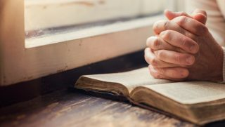 Hands clasped in prayer over an open Bible.