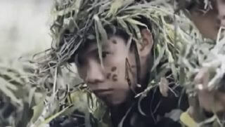 Vietnamese soldier hiding in grass