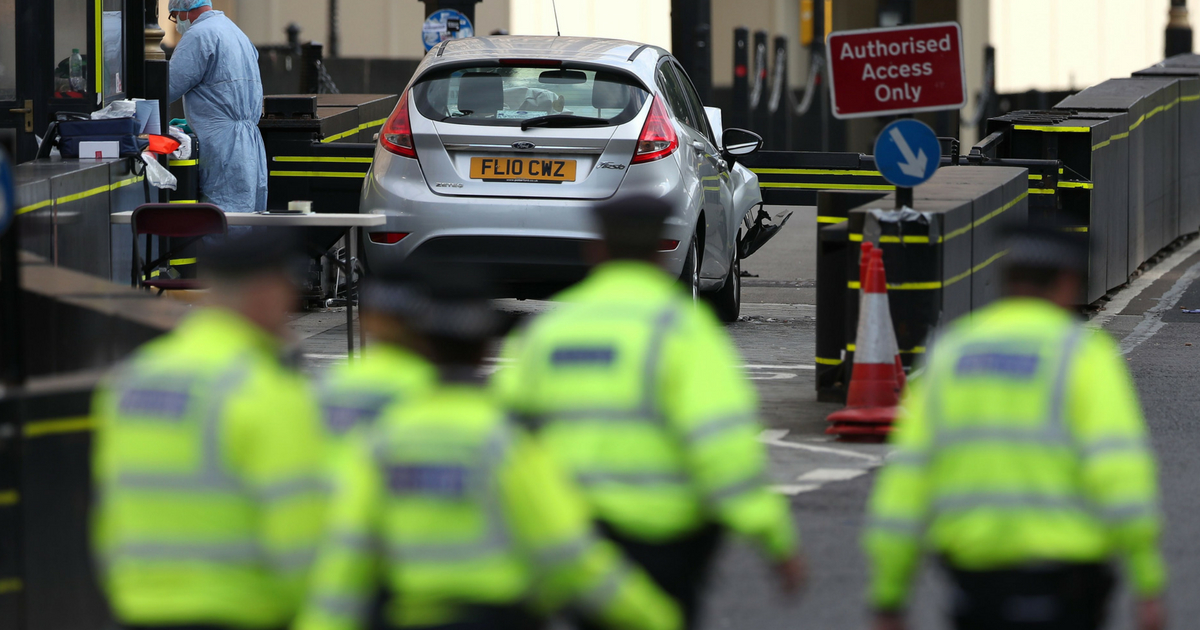 A police forensics officer works around a silver Ford Fiesta car that was driven into a barrier at the Houses of Parliament in central London on August 14, 2018. - A car crashed into barriers outside Britain's Houses of Parliament in a suspected terror attack on Tuesday, injuring a 'number of pedestrians' yards from where five people were killed last year.
