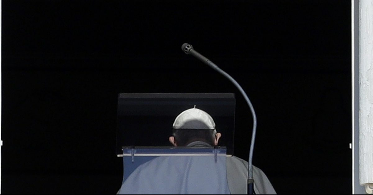 Pope Francis is viewed from behind against a dark backdropo.
