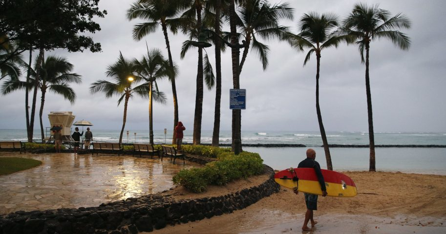 A surfer walks along Waikiki Beach in a light rain from Tropical Storm Lane, Saturday, Aug. 25, 2018, in Honolulu.