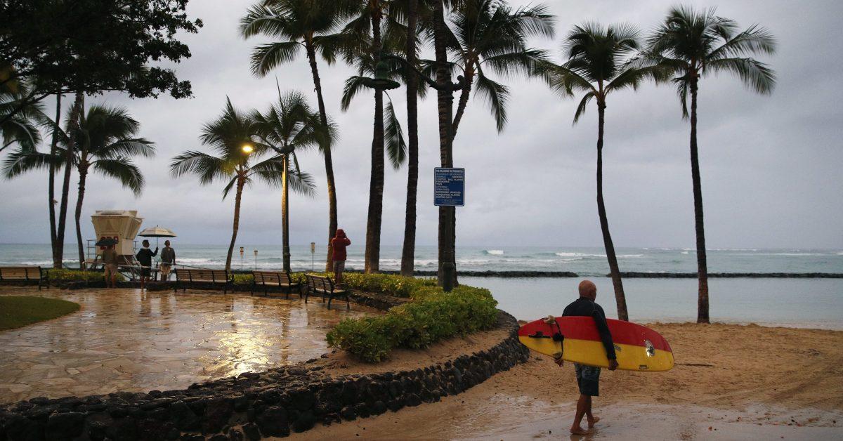 A surfer walks along Waikiki Beach in a light rain from Tropical Storm Lane, Saturday, Aug. 25, 2018, in Honolulu.