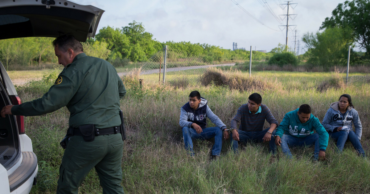 A Border Patrol agent apprehends four illegal immigrants shortly after they crossed the border from Mexico into the United States