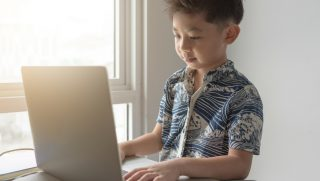 Little boy using a laptop.