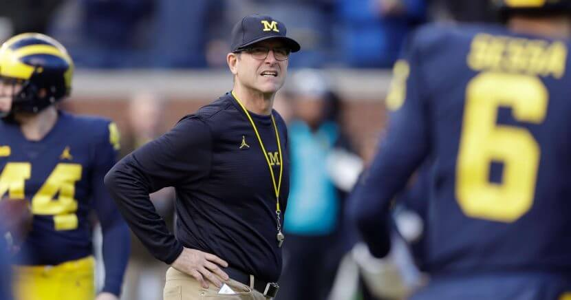 In this Nov. 25, 2017, file photo, Michigan coach Jim Harbaugh watches players warm up for an NCAA college football game against Ohio State in Ann Arbor, Mich.