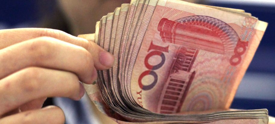 a bank clerk counts Chinese 100 Yuan notes in Shanghai
