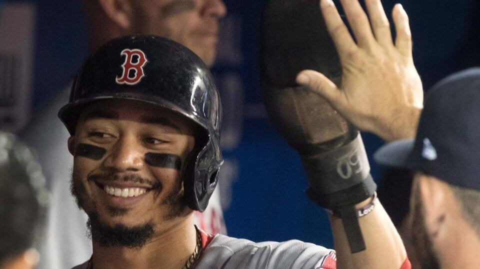 Boston Red Sox's Mookie Betts is congratulated in the dugout after scoring against the Toronto Blue Jays during the first inning of a baseball game Thursday, Aug. 9, 2018, in Toronto.