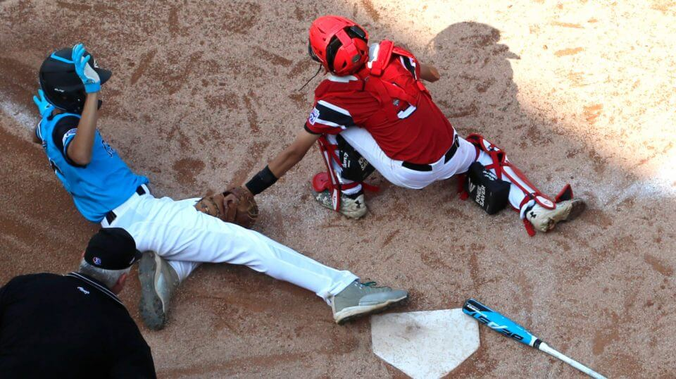 Canada catcher Andre Juco tags out Puerto Rico's Carlos De Jesus (17) at home during the fourth inning of Little League World Series baseball tournament game in South Williamsport, Pa., on Wednesday.