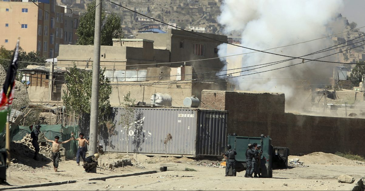 Smoke rises from a house where suspected attackers were hiding while policemen arrest two suspects, left, in Kabul, Afghanistan, Tuesday. The Taliban fired rockets toward the presidential palace in Kabul Tuesday as President Ashraf Ghani was giving his holiday message for the Muslim celebrations of Eid al-Adha. (AP Photo/Rahmat Gul)