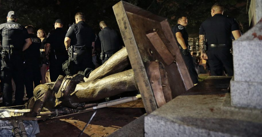 Police stand guard after the Confederate statue known as Silent Sam was toppled by protesters on campus at the University of North Carolina in Chapel Hill, N.C., on Aug. 20, 2018.