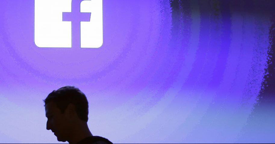 Silhuette of Markk Zuckerberg against Facebook sign.