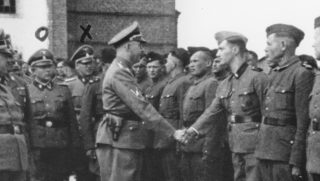 Black and white photo of Nazi leader Heinrich Himmler shaking hands with line of guards.