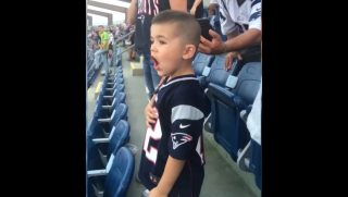 Little boy wearing Patriots jersey singing loudly