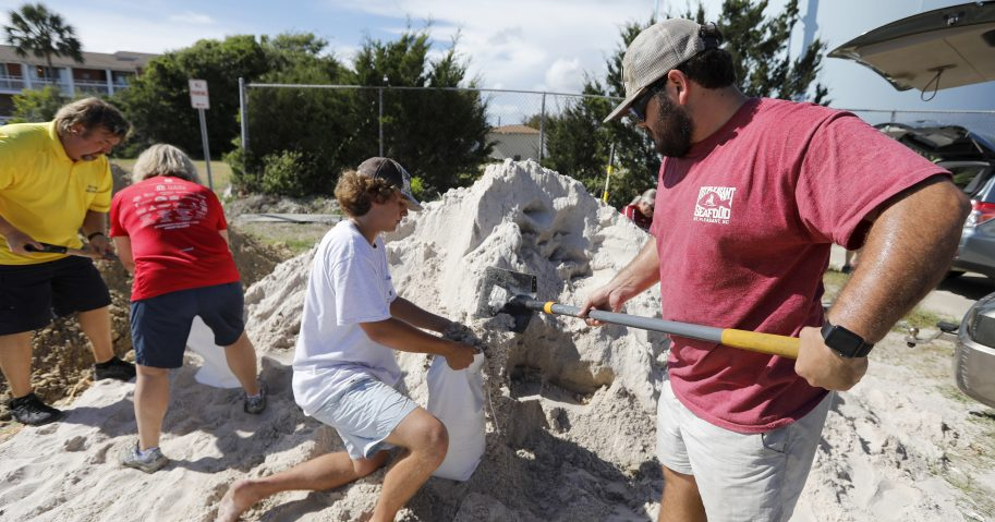 Walker Townsend from the Isle of Palms, S.C., fills a sand bag while Dalton Trout holds the bag at the Isle of Palms municipal lot where the city was giving away free sand in preparation for Hurricane Florence.