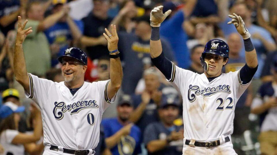 The Milwaukee Brewers' Christian Yelich (22) celebrates with Ed Sedar (0) after hitting a two-RBI triple during the sixth inning against the Cincinnati Reds on Monday in Milwaukee.