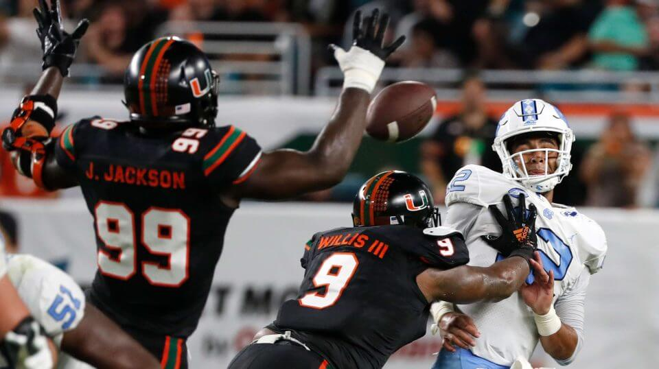 Miami defensive linemen Joe Jackson (99) and Gerald Willis III (9) rush North Carolina quarterback Chazz Surratt (12) as he attempts to pass during the first half of the Hurricanes' home game Thursday night.