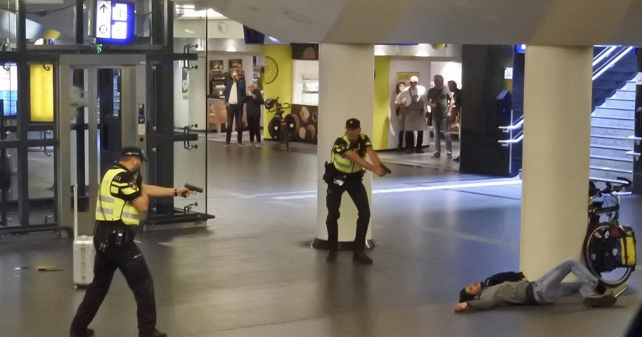 Dutch police officers point their guns at a wounded 19-year-old man who was shot by police after stabbing two people in the central railway station in Amsterdam, the Netherlands Friday Aug. 31, 2018.
