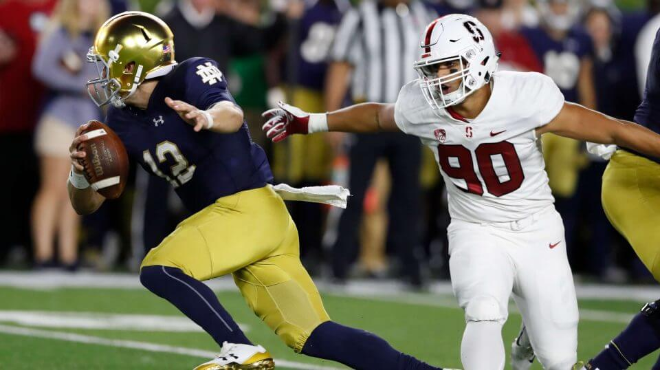 Notre Dame quarterback Ian Book scrambles away from Stanford linebacker Gabe Reid (90) during the first half of Satruday's game in South Bend, Indiana.