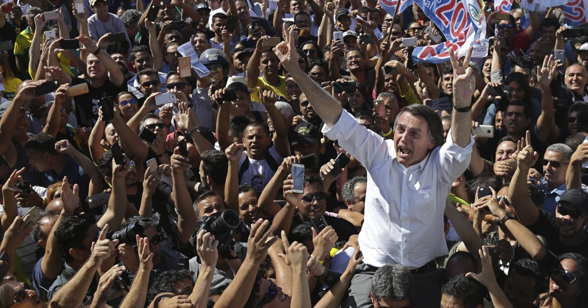National Social Liberal Party presidential candidate Jair Bolsonaro greets supporters as he gets a shoulder ride from a member of his security detail Wednesday.