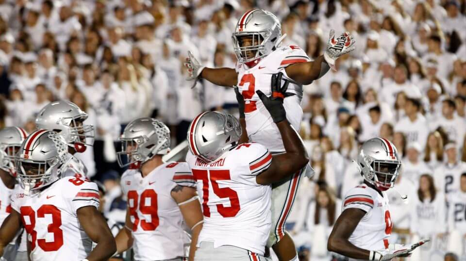 Ohio State's J.K. Dobbins (2) is lifted up by teammate Thayer Munford (75) after scoring against Penn State on Saturday.