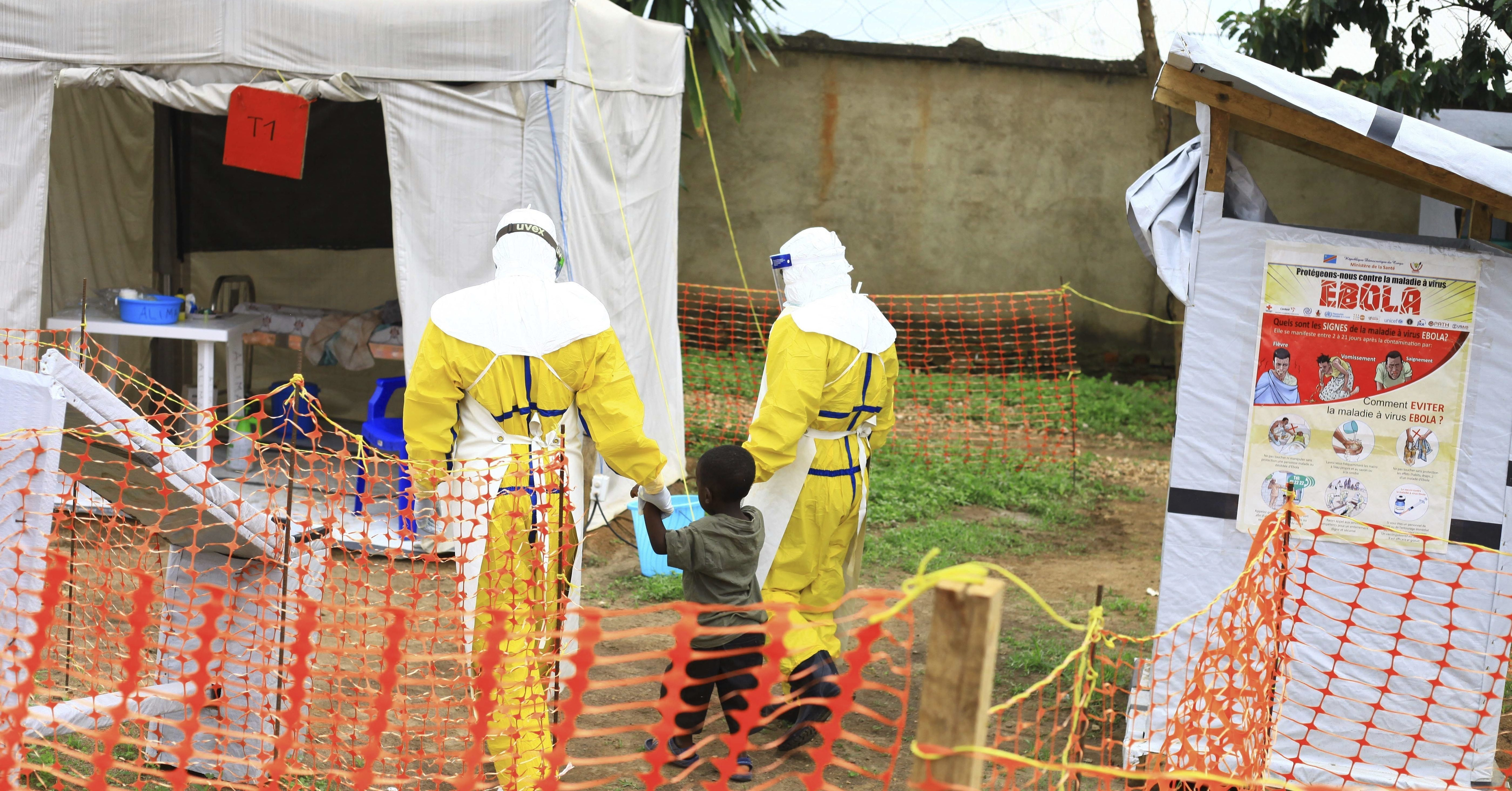 Health workers walk with a boy suspected of having the Ebola virus Sept. 9 at an Ebola treatment center in Beni, Eastern Congo.
