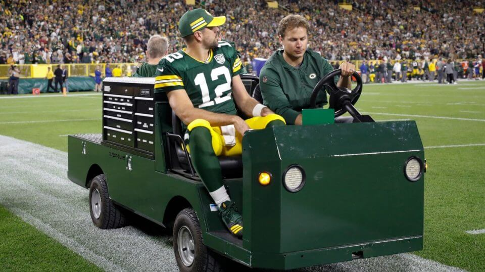 Packers quarterback Aaron Rodgers is taken off the field on a cart after injuring his leg during the first half of Sunday's game against the Chicago Bears in Green Bay.