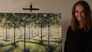 Girl stands next to her painting of a grove of trees.