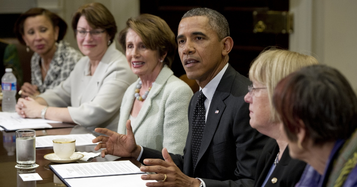 President Barack Obama talks to women of Congress, including House Democratic Leader Nancy Pelosi on March 12, 2014.