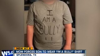 "Boy wearing T-shirt that says ""I am a bully"" in all uppercase letters."