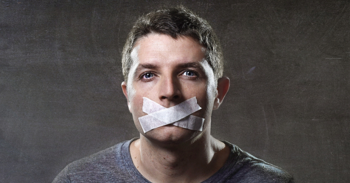 A man with duct tape over his mouth to reflect censorship.