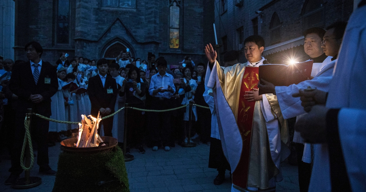 Chinese Catholic Bishop Zhang Hong blesses the flame used to light the Paschal Candle at a mass on Holy Saturday during Easter celebrations at the government-sanctioned West Beijing Catholic Church on April 15, 2017.