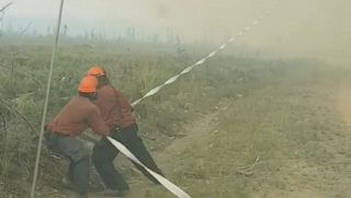 "Firefighters in British Columbia, Canada, struggle to hold onto their hose against the might of a ""firenado,"" a vortex of flames."