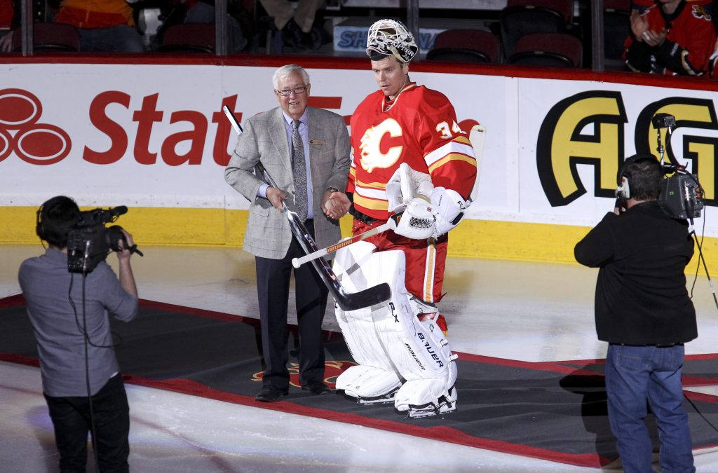 Miikka Kiprusoff #34 of the Calgary Flames receives a silver stick from Clay Riddell.