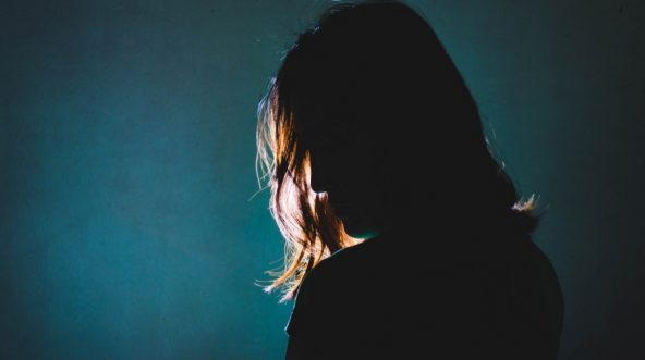 Silhouette of depressed woman standing in the dark with light shining behind.