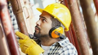 Man wearing hard hat and gloves works in a construction job.