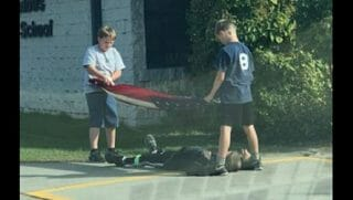 Two boys fold a flag while another lies beneat to make sure it doesn't touch the ground.