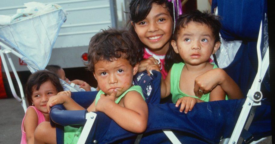 Latino children pose in a stroller in California