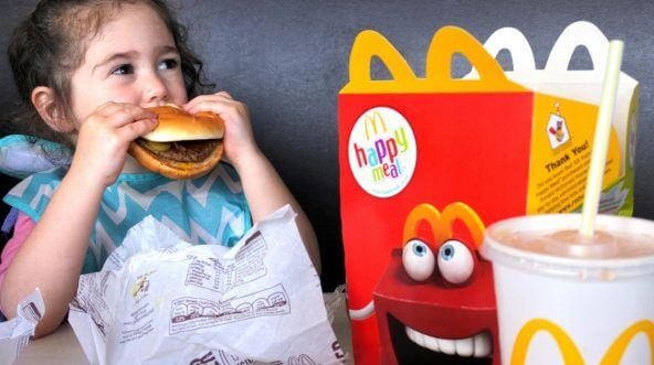 A young girl eats a hamburger from her kids meal at McDonald's