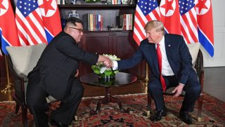 U.S. President Donald Trump, right, shakes hands with North Korea's leader Kim Jong Un, left, as they sit down for their historic U.S.-North Korea summit.