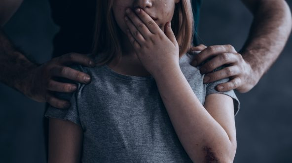 Little girl with hand over her mouth and a man's hands on her shoulders.