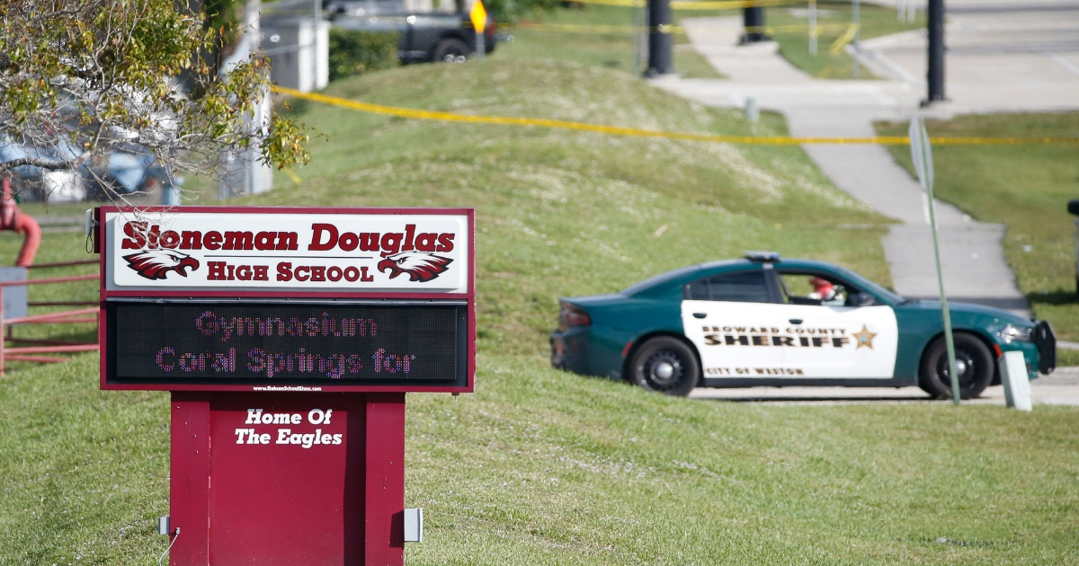 Law enforcement officers block off the entrance to Marjory Stoneman Douglas High School in Parkland, Florida, one day after a shooting claimed the lives of 17 students and staff.